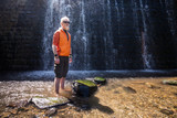 Young man with a blonde hair and beard standing in front of a waterfall