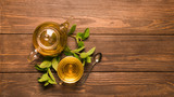 Tea in a transparent cup and teapot from fresh melissa leaves on a wooden background. - 222322752