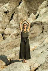 young beautiful woman stands with arms raised over her head, in a namaste position, outdoor against a background of desert rocks..