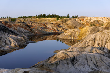 landscape - lake at the bottom of a spent quarry of kaolin mining with beautiful slopes with traces of streams
