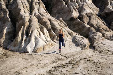 young slender athletic girl runs along a rough, deserted mountainous terrain