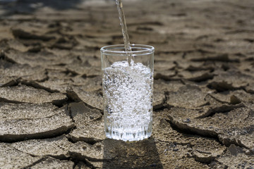 pure clear fresh water is poured into a glass beaker standing in the middle of a dry cracked clay desert land