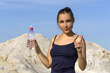 young slender athletic girl after playing sports outdoors holds a plastic water bottle and gestures to emphasize the importance of drinking water
