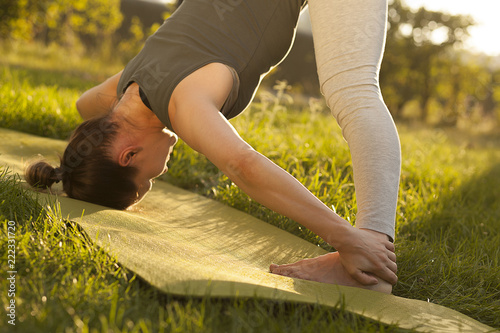 Poster Practice of yoga and gymnastics. Young girl doing yoga. Female yoga. Yoga in the Summer Park