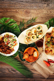 various street food with pani puri, chicken wings and coxinha on rustic background. balinese nasi campur and indian street food