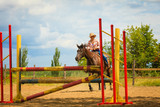 Cowgirl in western hat doing horse jumping - 222358516