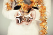 Woman hands close up holding christmas decoration stars, cozy sweater with golden christmas garland
