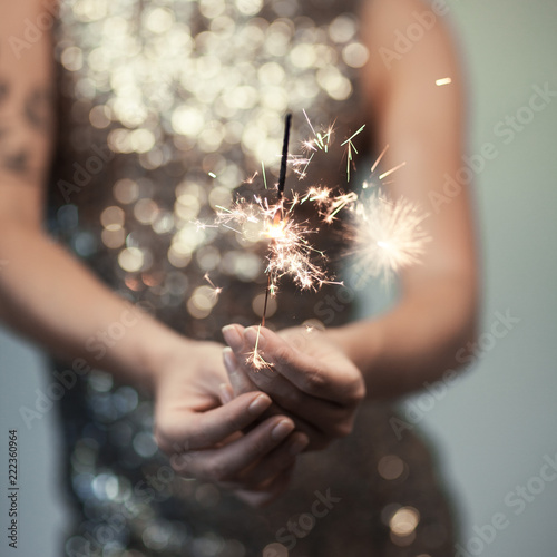 Leinwanddruck Bild woman in glitter dress holding sparkler, close up hands, romantic look, can be used as background