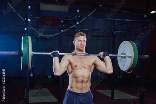 Mięśni fitness człowiek przygotowuje się do martwego ciągu sztangą nad głową w nowoczesnym centrum fitness. Funkcjonalny trening. Ćwicz ćwiczenia. Cross style fit, deadlift