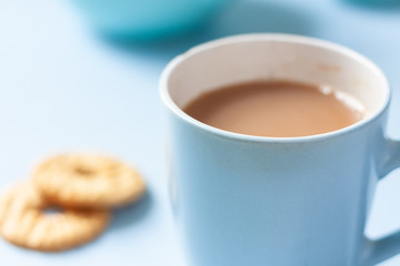 A blue mug of tea and biscuits with tea pot and accessories on a pale blue background