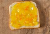 orange jam spread over white slice of bread
