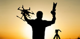 man holds a drone end photocamera in the hands of the setting sun - 222369373