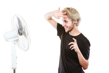 Young man fighting with wind from cooling fan © anetlanda