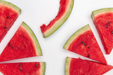 Sliced watermelon pieces with one eaten on white background