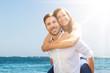 Leinwanddruck Bild - Happy Man Giving Piggyback To His Wife At Beach
