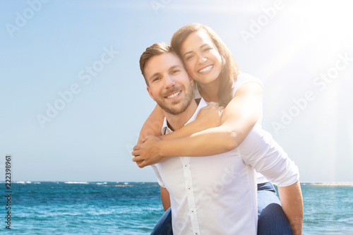Foto Murales Happy Man Giving Piggyback To His Wife At Beach