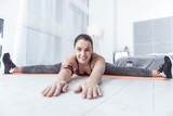 Flexible body. Delighted fit woman smiling while developing her flexibility - 222408138
