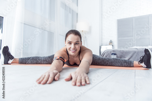 Wall mural Flexible body. Delighted fit woman smiling while developing her flexibility