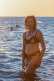 Portrait of a girl in the sea at sunset