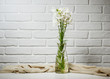 Quadro white flower in a vase is on the table with knitting woolen, brick wall background