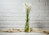 white flower in a vase is on the table with knitting woolen, brick wall background