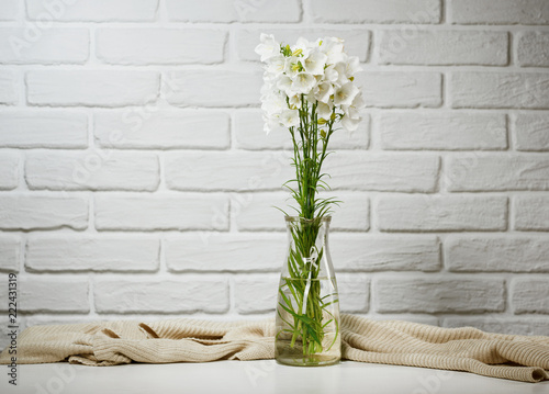 Foto Murales white flower in a vase is on the table with knitting woolen, brick wall background