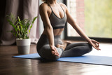 Young sporty woman practicing yoga, doing Ardha Padmasana exercise, Half Lotus pose, working out wearing sportswear, grey pants and top, indoor close up, yoga studio. Healthy mindful lifestyle concept