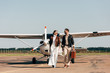 stylish young couple in leather jackets and sunglasses walking with retro suitcase near airplane