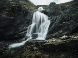 Waterfall between sharp exposed rocks, in Norway. Trek by popular footpath by crystal clear river. Cold water falling from the steps of shar