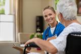 Friendly nurse talking to senior patient - 222437117
