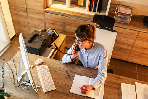 Foto Murales Businesswoman in her office.She sitting at the desk and talking on the phone.