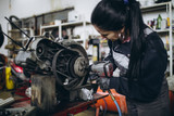 Strong and worthy woman doing hard job in car and motorcycle repair shop. - 222453507