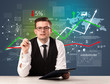 Leinwanddruck Bild - Young handsome businessman sitting at a desk with stocks and progress charts behind him