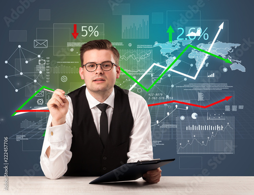 Leinwanddruck Bild Young handsome businessman sitting at a desk with stocks and progress charts behind him