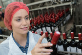 female worker using machine to work at wine factory - 222458728
