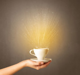 Young female hand holding coffee cup with a beam of light rising out of it  - 222462324
