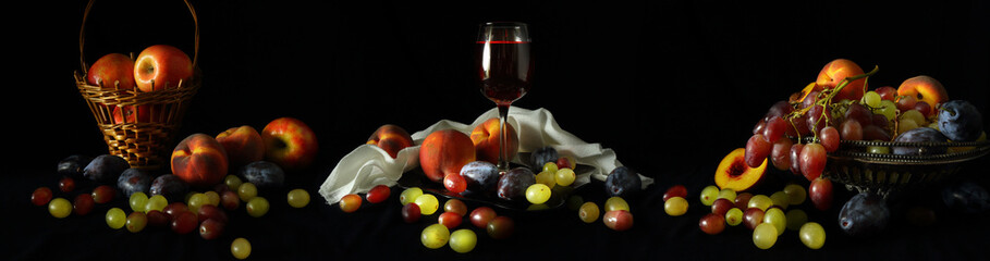 Large-format panorama with a glass of wine and fruit on a dark background © parsadanov
