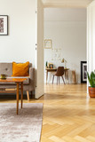View from the living room with herringbone parquet floor into a home office interior with golden organizer above a wooden desk - 222474127