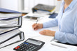 Leinwanddruck Bild - Calculator and binders with papers are waiting to be processed by business woman or bookkeeper back in blur. Internal Audit and tax concept
