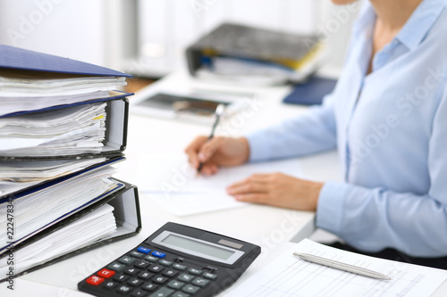 Leinwanddruck Bild Calculator and binders with papers are waiting to be processed by business woman or bookkeeper back in blur. Internal Audit and tax concept