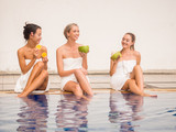 Beautiful woman wrapped with towel.petty girls holding coconut and slide orange.happy female talking together near swimming pool.