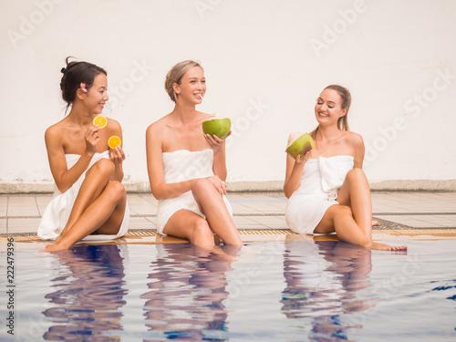 Piękna kobieta zawijająca z towel.petty dziewczynami trzyma koksu i obruszenia pomarańcze szczęśliwa kobieta opowiada wpólnie blisko pływackiego basenu.