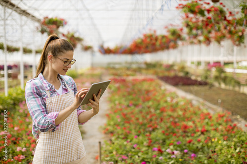 Sticker Young woman using tablet in green garden