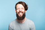 happiness enjoyment and laugh. exhilarated man with a wide grin. portrait of a young bearded hipster guy on blue background. emotion facial expression. feelings and people reaction. - 222483540