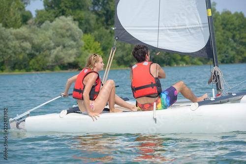 couple having a sailing lesson on a lake