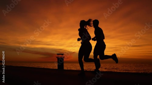 SILHOUETTE: Unrecognizable young man and woman exercising together by the ocean. Athletic joggers enjoying a picturesque run along the scenic coastal trail by ocean. Runners training on summer evening © helivideo