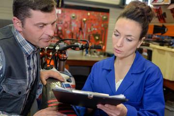 Mechanics checking paperwork on clipboard
