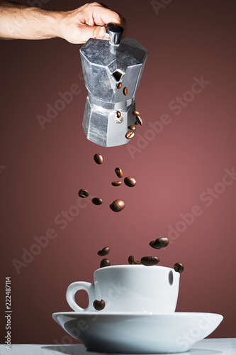 Coffee pot pouring roasted coffee beans into the cup - 222487114