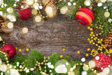 christmas red decorations and fir tree frame on wooden background with light beams - 222487593