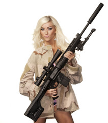 Beautiful young blonde model holding army style machine gun